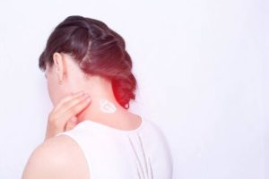 The girl smears her neck with a healing cream to relieve muscle tension and pain. Treatment of cervical spinal diseases, copy space, vertebral instability Banque d'images - 132200258